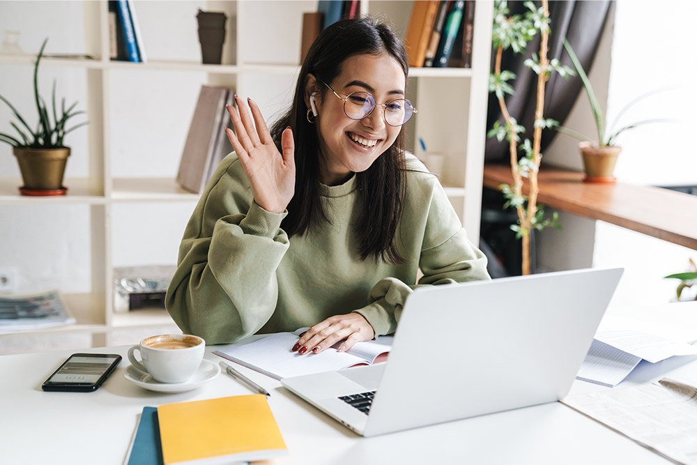 a woman in her home office, working from home during a video conference; how-to for virtual meetings