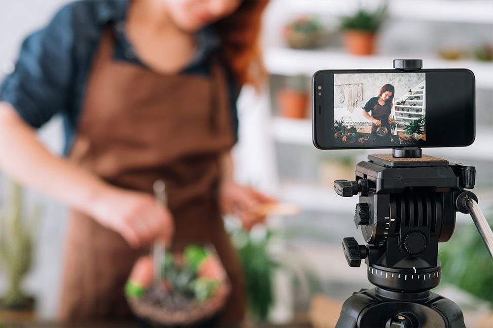 A woman in a leather apron films a video for her content marketing strategy